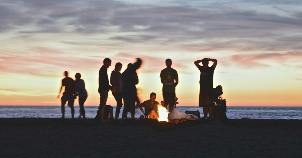 friends around fire on beach