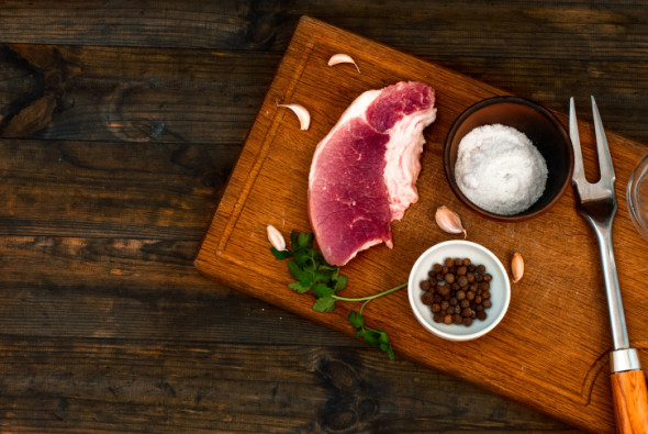 Raw fresh meat steak on kitchen cutting board on a dark wood   background