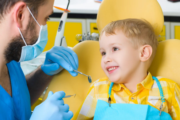 Close up of boy having his teeth examined by a
