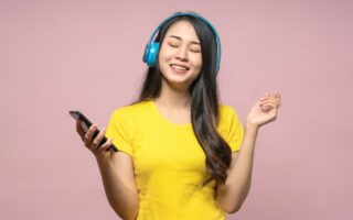 woman listening to music in wireless headphone with smartphone
