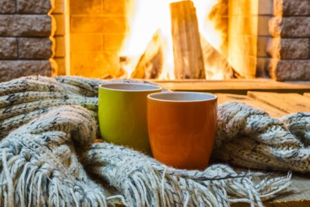 Mugs for tea or coffee near fireplace